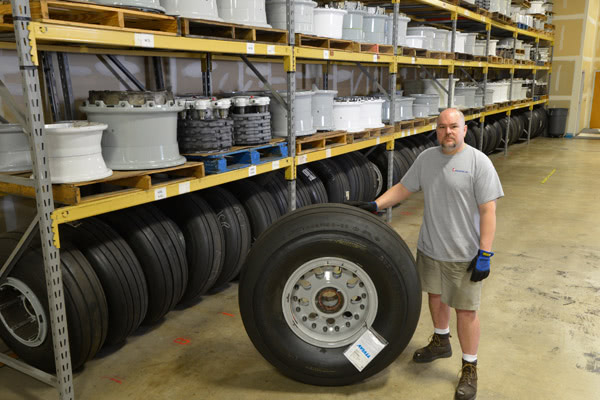 An employee next to an airplane tire